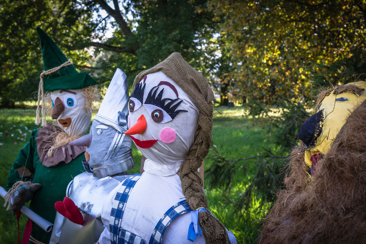 Close-up of scarecrows on field against trees