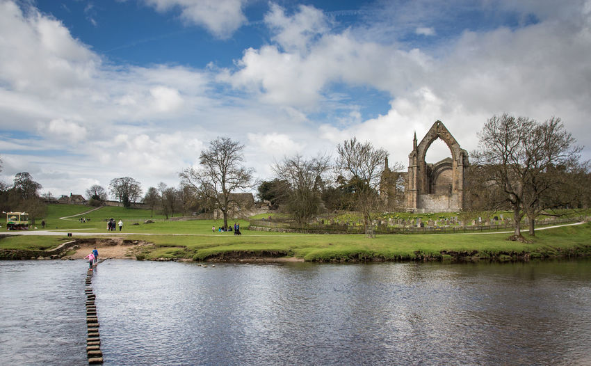 Scenic view of stepping stones in bolton abbey  against blue sky with clouds