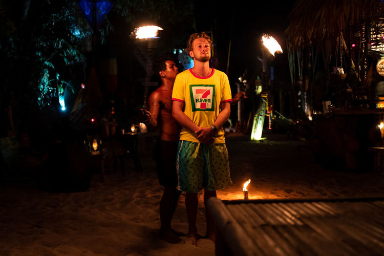 Koh Lipe Night Illuminated One Person Front View Real People Standing Lifestyles Incidental People Casual Clothing Looking At Camera Men Full Length Lighting Equipment City Architecture Holding Adult Leisure Activity Celebration