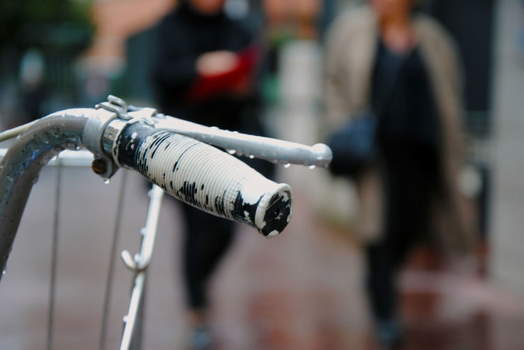 Close-up of wet bicycle handle on street