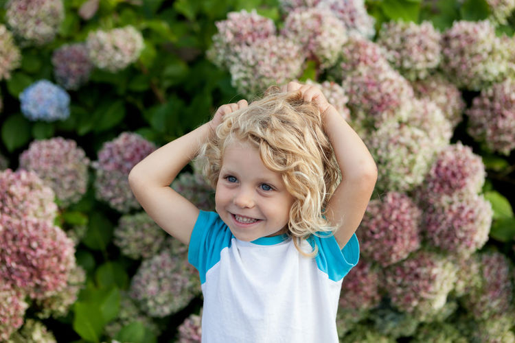 Cute girl with hands in hair standing against plants