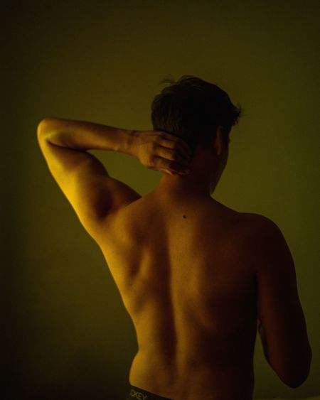Rear view of shirtless man standing against gray background