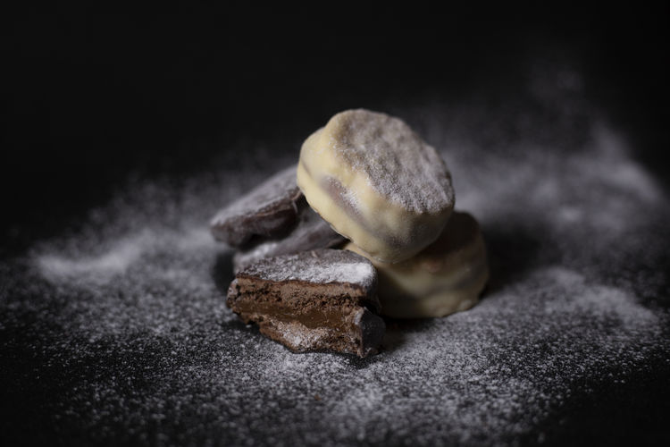 Macro with black background of four chocolate alfajores stuffed with dulce de leche and covered by sugar Sweet Food Food Sweet Indoors  Dessert No People Temptation Close-up Unhealthy Eating Studio Shot Black Background Selective Focus Powdered Sugar Powder Yummy Delicious Dulce De Leche Chocolate Alfajor Pastry Gourmet Food Styling Foodphotography