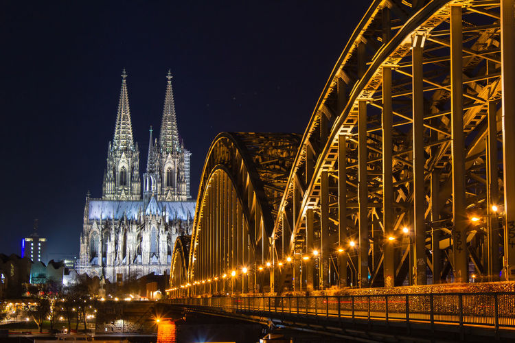 Cologne skyline with Cologne Cathedral and Hohenzollern bridge at night Cologne Cologne Cathedral Cathedral Built Structure Architecture Night Illuminated Building Exterior Travel Destinations City Building Place Of Worship Sky Religion Bridge Connection Spirituality Belief Bridge - Man Made Structure Nature Transportation No People Outdoors Office Building Exterior Spire