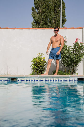 Full length of shirtless man in swimming pool