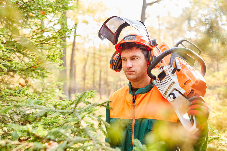 Man carrying chainsaw while standing in forest