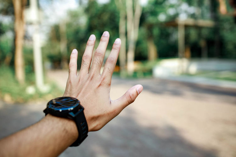 Cropped image of hand with wristwatch against blurred background