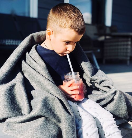 Cute boy drinking smoothie in city