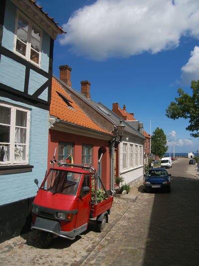 Cars on road by buildings against sky