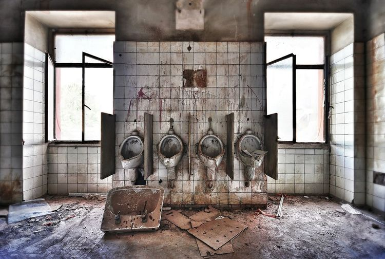 Damaged urinals in abandoned building