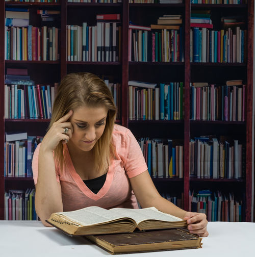 Young woman reading book while sitting at library