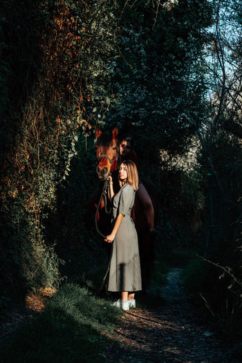 Full length portrait of woman with horse standing in forest