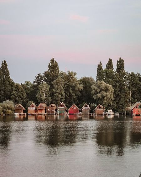 Houses by river against buildings and trees against sky