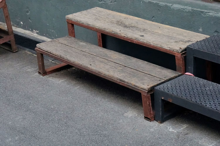 High angle view of empty bench on table against building