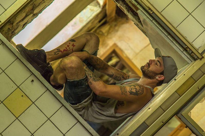 Tilt shot of hipster sitting on window frame in abandoned building