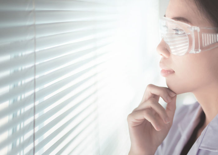 Close-up of young woman looking through blinds