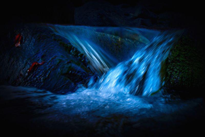 Water flowing through rocks at night