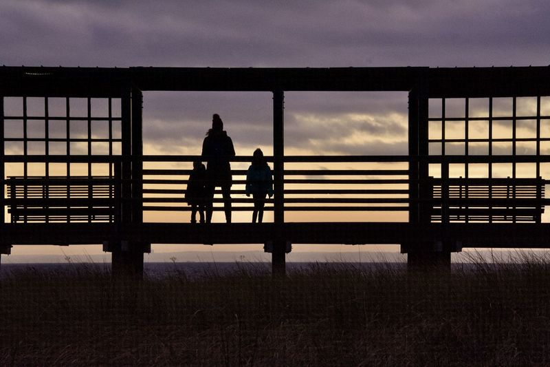 Silhouette people on railing against sky during sunset