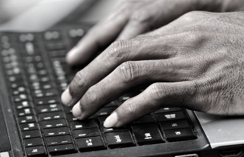 Close-up of man using laptop