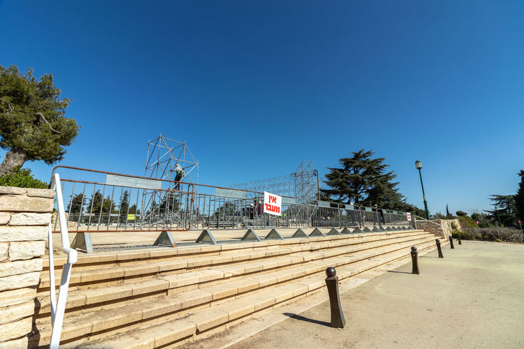 Text on railing against clear blue sky