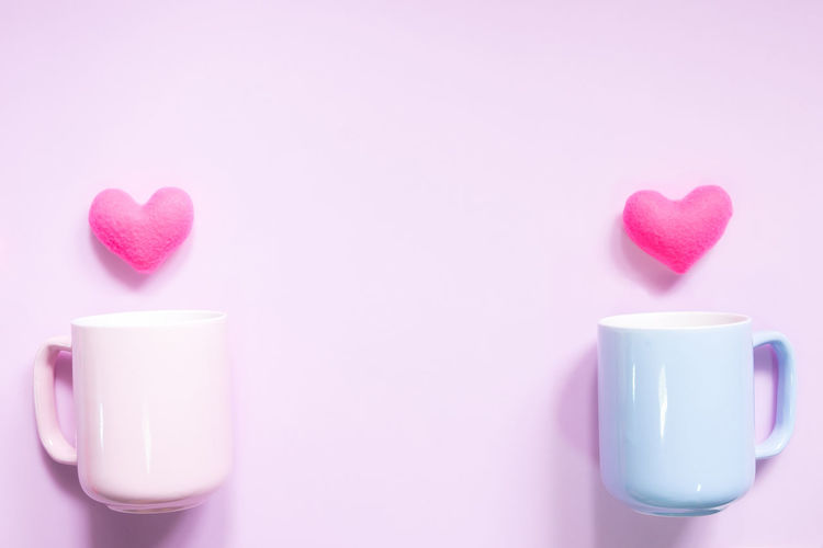 Cup with heart shape decorations over pink background