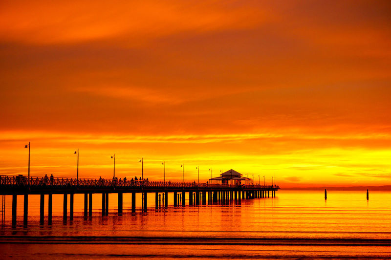 Silhouette pier over sea against orange sky