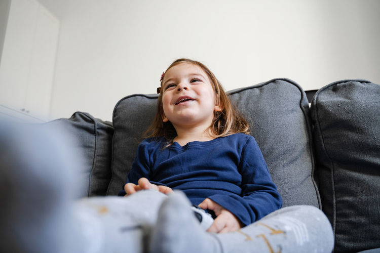 Smiling girl holding joystick playing game sitting on sofa