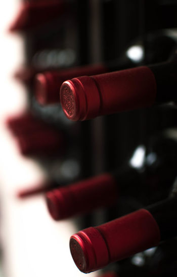 Close-up of red wine bottles on rack