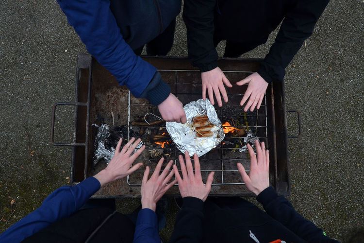 People warming hands by barbecue grill