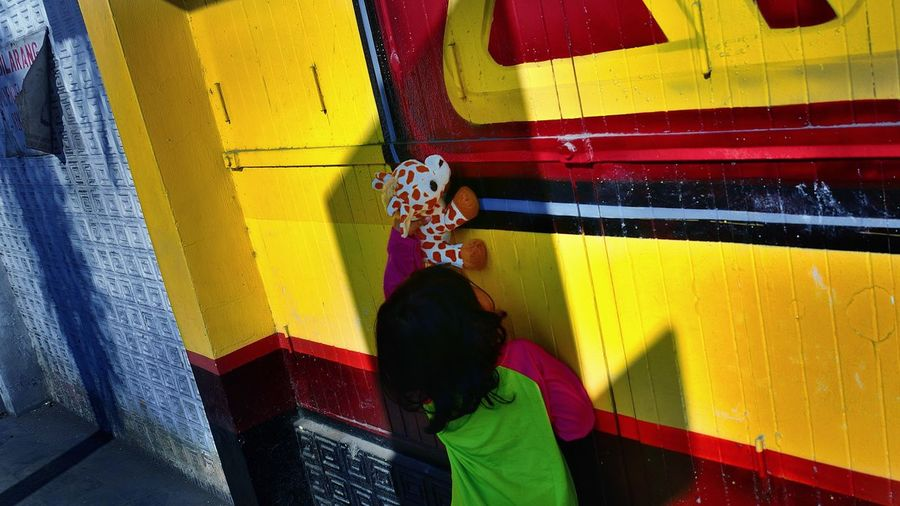 Rear view of boy with stuffed toy against yellow wall