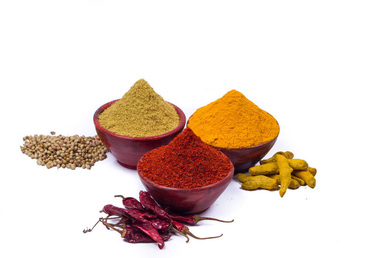 High angle view of various spices in bowls on white background
