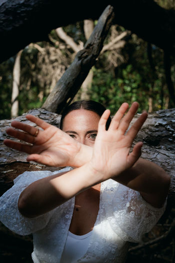 Portrait of woman with hand on tree