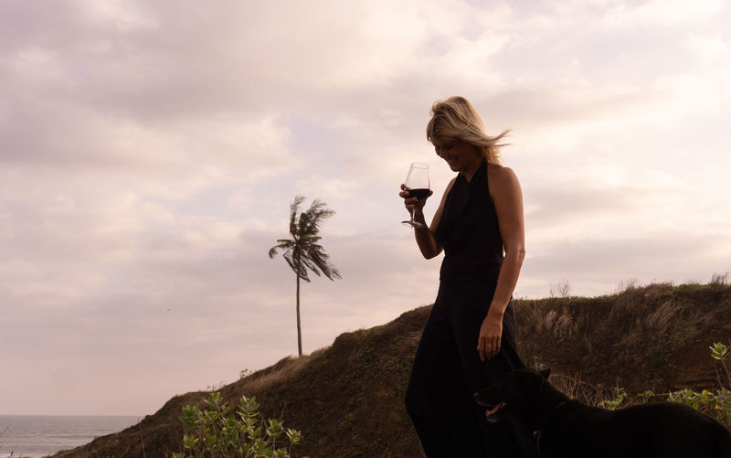 Woman drinking wine while standing on land against sky