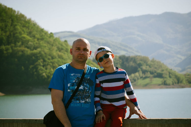 Portrait Of Man With Son Against Lake And Mountains