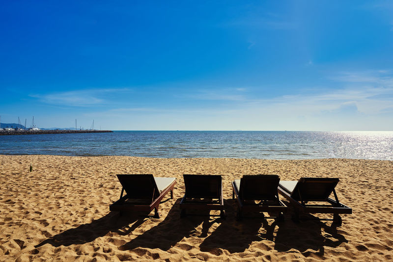 Summer beach view and wooden deck chair on sand for relaxation with blue sky and ocean Summer Views Sunbeds On The Beach Beach Deckchairs On The Sand Outdoors Pattaya Beach Relaxation Time Sand & Sea Seaside Beach Sea Sunny Day