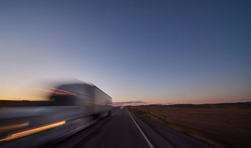 Blurred motion of road against clear sky during sunset