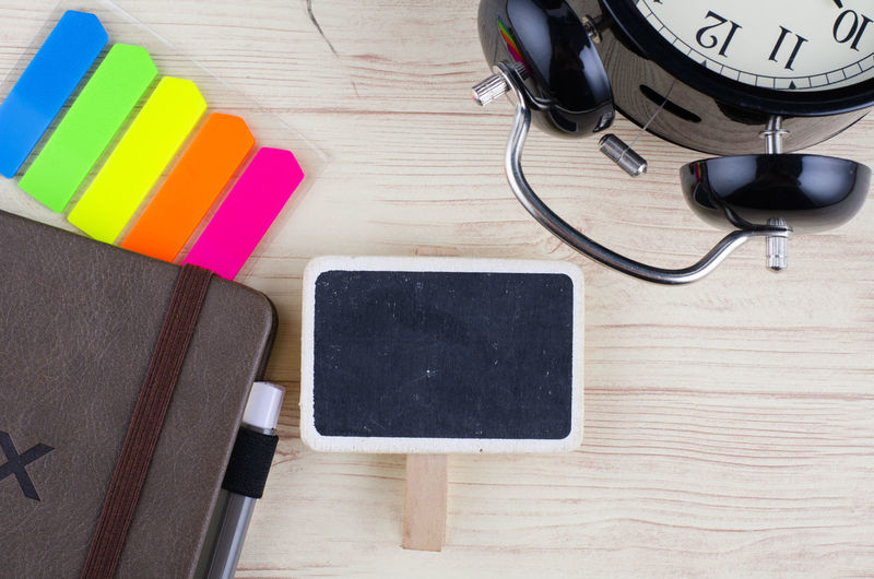 template background with wooden signage for text, alarm clock, sticky paper and diary on desk Table Technology Still Life High Angle View Multi Colored Indoors  Wireless Technology Connection Pen Computer No People Wood - Material Black Color Communication Close-up Portable Information Device Computer Equipment Screen Desk Writing Instrument Wood