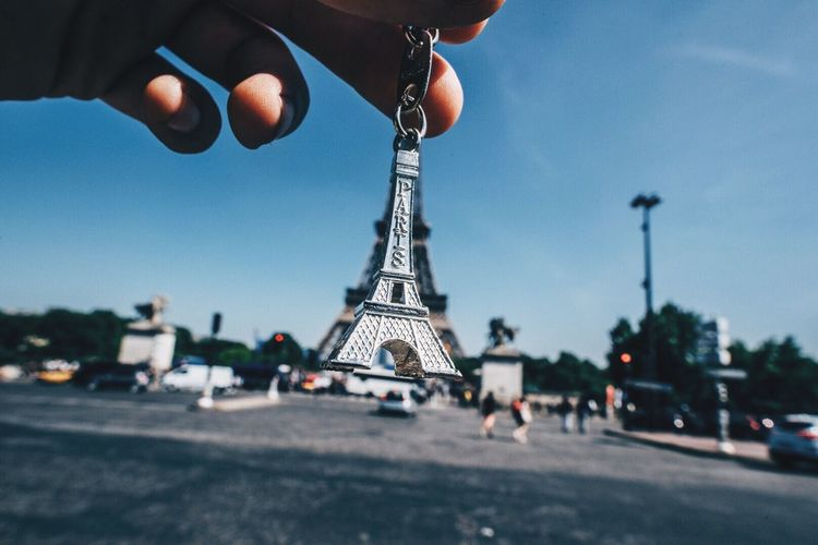 Cropped image of hand holding key ring against eiffel tower