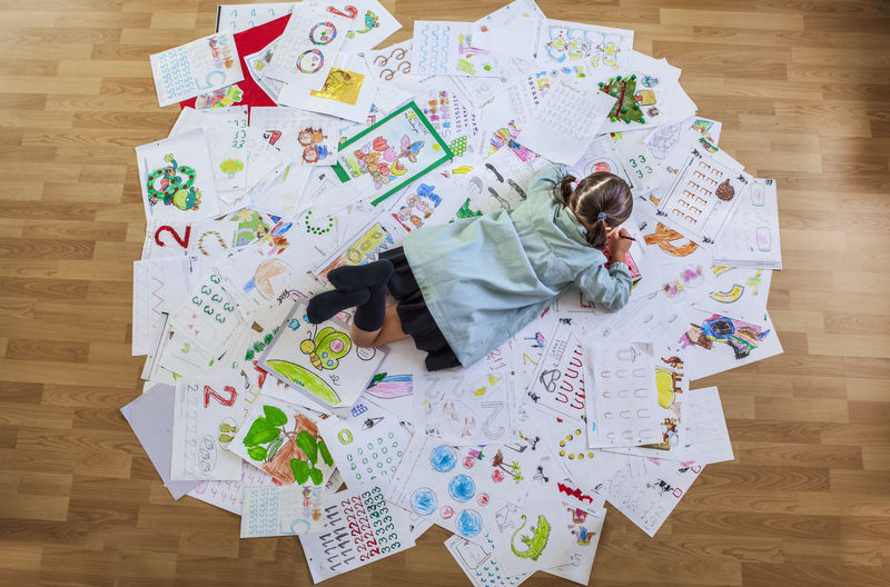 High Angle View Of Girl On Drawing Papers At Home