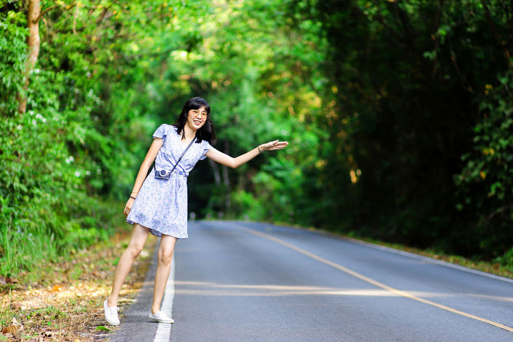 Beautiful day at Khao Yai National Park Transportation Plant Casual Clothing Young Women Tree Day Nature Lifestyles Leisure Activity Women Outdoors Adult Beautiful Woman Khao Yai National Park Thailand Woman Travel Girl Asian  Park Forest Camera Fern Tree Road Waving