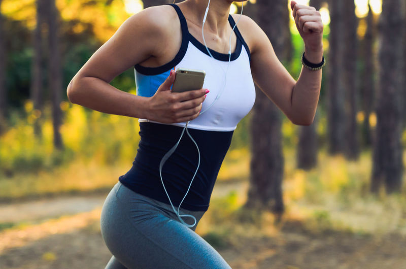Midsection Of Woman Running With Smart Phone