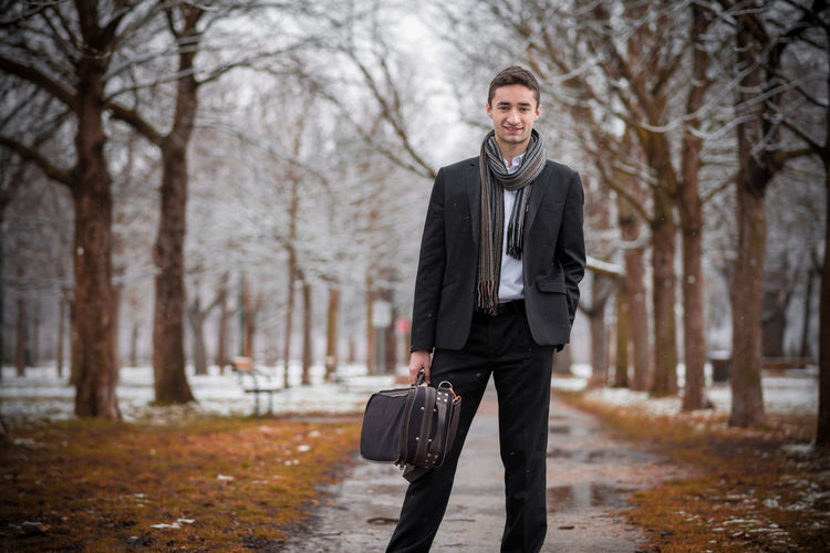Portrait of businessman standing against bare trees during winter