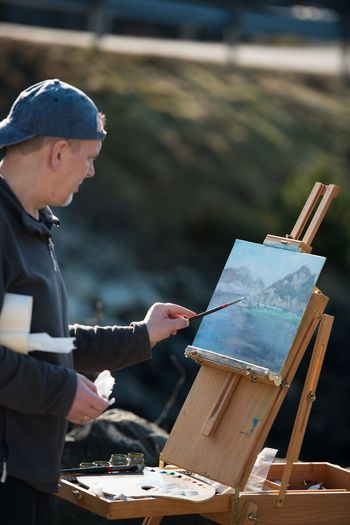 Man artist drawing on canvas with oil in nature Oilpainting Drawing Artist One Person Side View Men Day Focus On Foreground Three Quarter Length Adult Outdoors Real People Business Males  Working Lifestyles Casual Clothing Nature