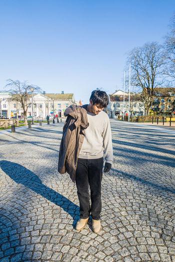 Full length of teenage girl standing on footpath