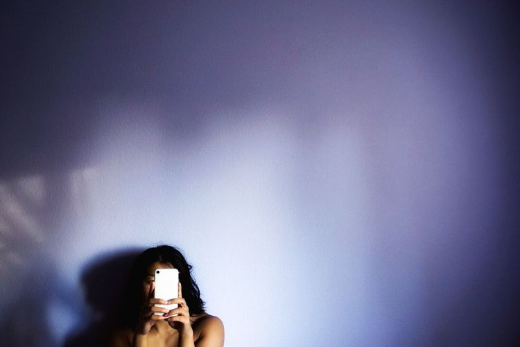 Shirtless woman using phone by white wall