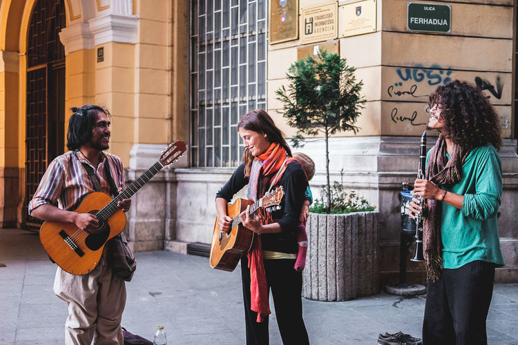 People playing guitar in city