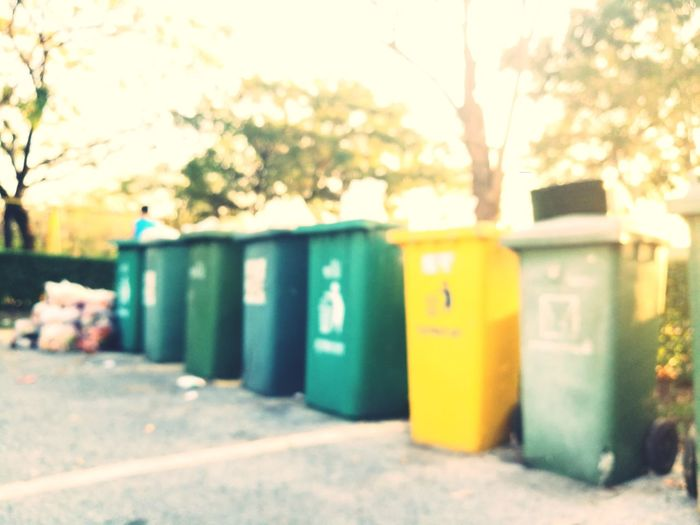 A blurry photo of overloaded garbage bins. Blurry Photo Garbage Bin Waste Management Waste Disposal Yellow Green Solidwastes Pollution Environmental Issues Segregation  Collection Mail Day Tree Public Mailbox Nature City