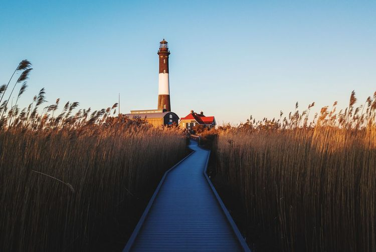 Boardwalk to fire island lighthouse against sky