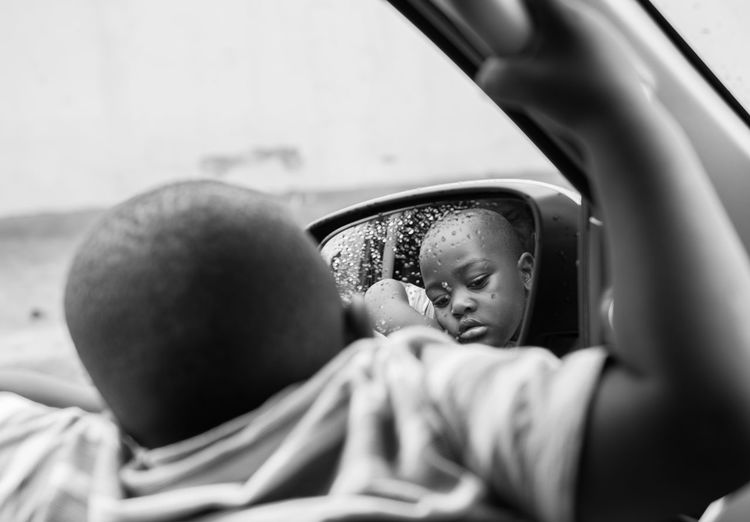 Close-up of boy with reflection on side-view mirror