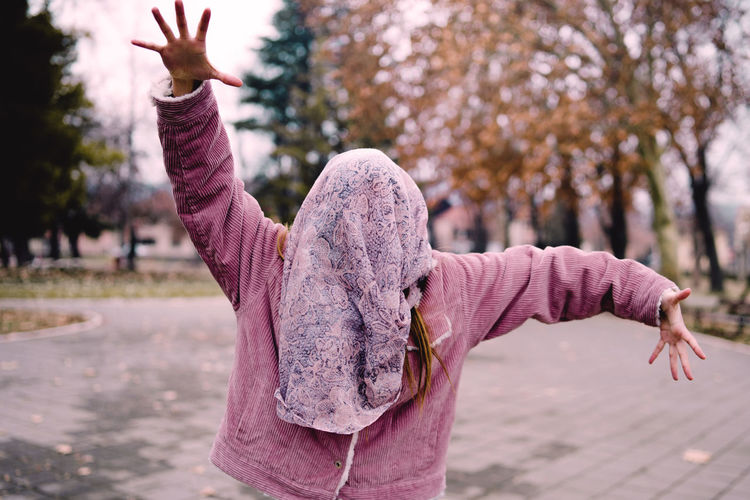 Girl with arms outstretched wearing fabric over face while standing on footpath